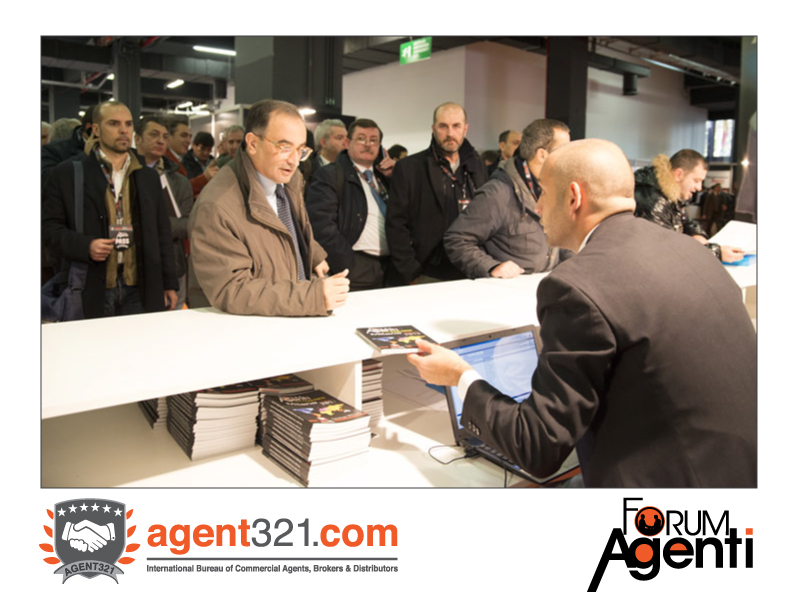 An Agent receives the Catalogue of the Exhibition